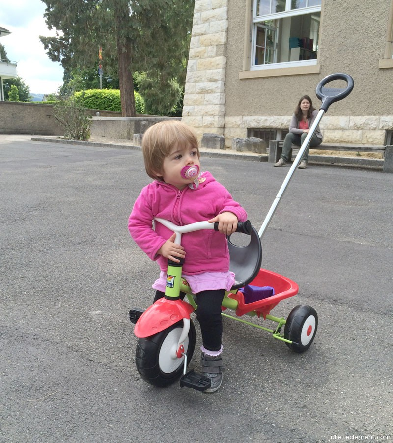Down at the playground, trying out her new trike