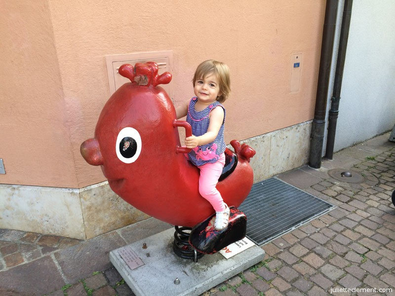 Juliette rides the giant sausage outside our local butcher