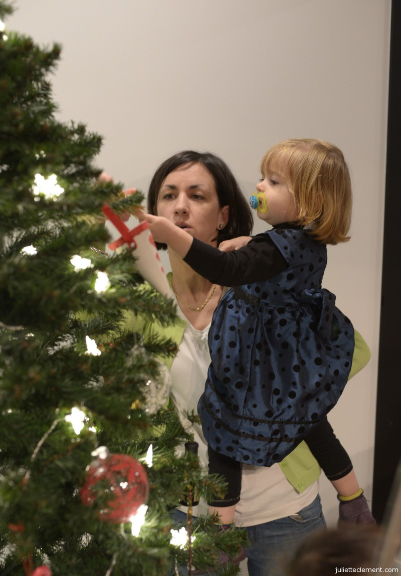 Juliette finds the perfect spot for her ornament, with a helping hand from Marjo