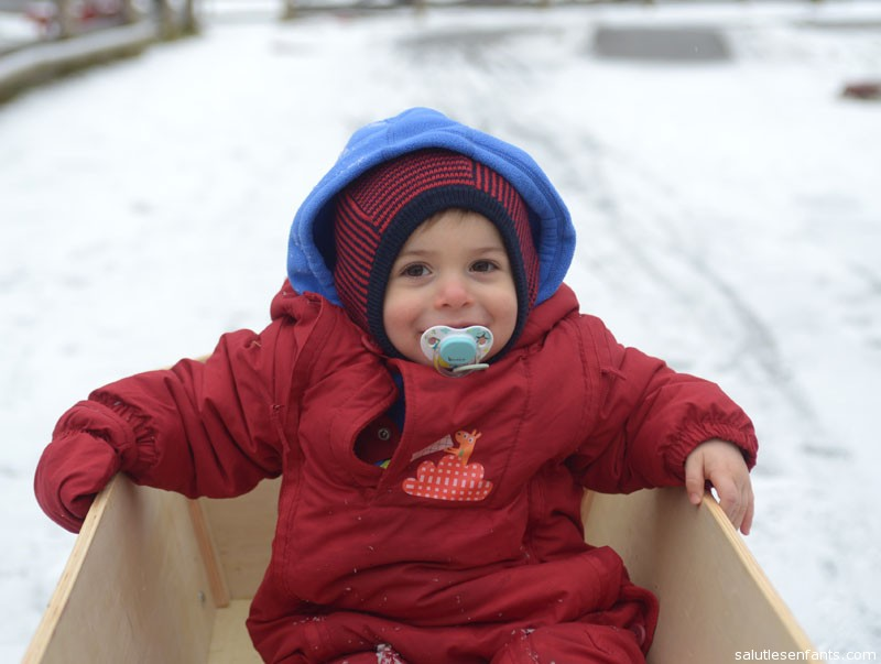 Alex takes a wagon ride in the snow.